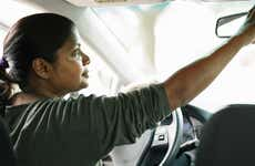 Woman checking rearview mirror of vehicle