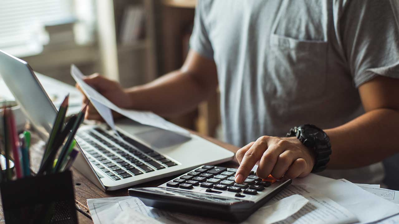 Man calculating bills in home office