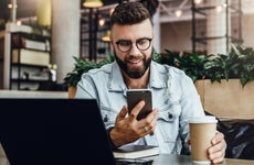 Bearded man working on laptop and phone