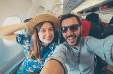Young couple take selfie on airplane