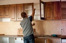 Man installs cabinets