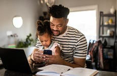 A father holds his daughter while looking at his phone