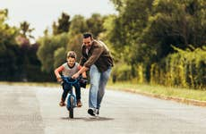 Father teaching son to ride a bicycle