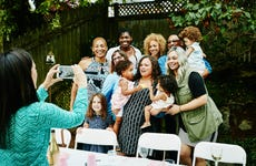 Woman taking photo with smartphone of smiling multi-generation family at backyard birthday party