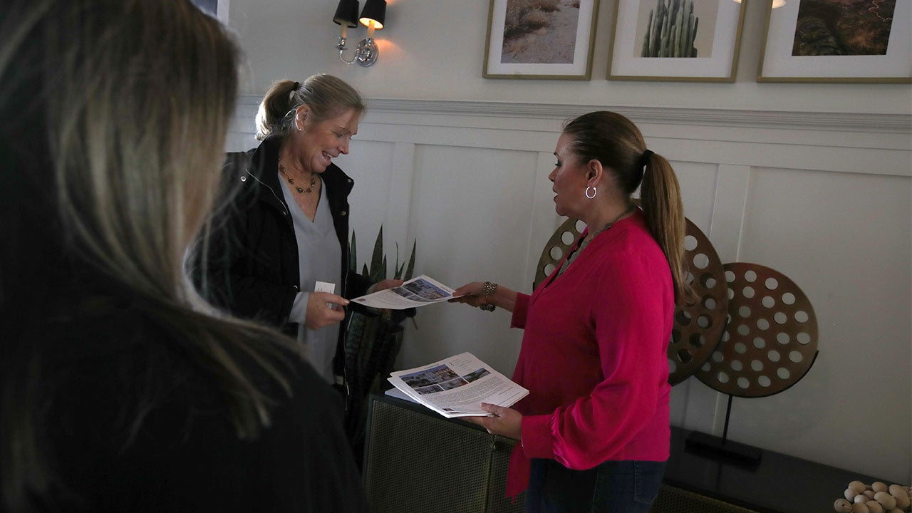 Women working with realtor and an open house