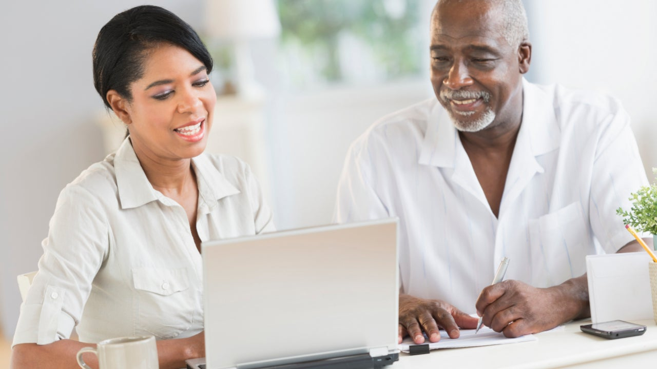 Two people look at a laptop.
