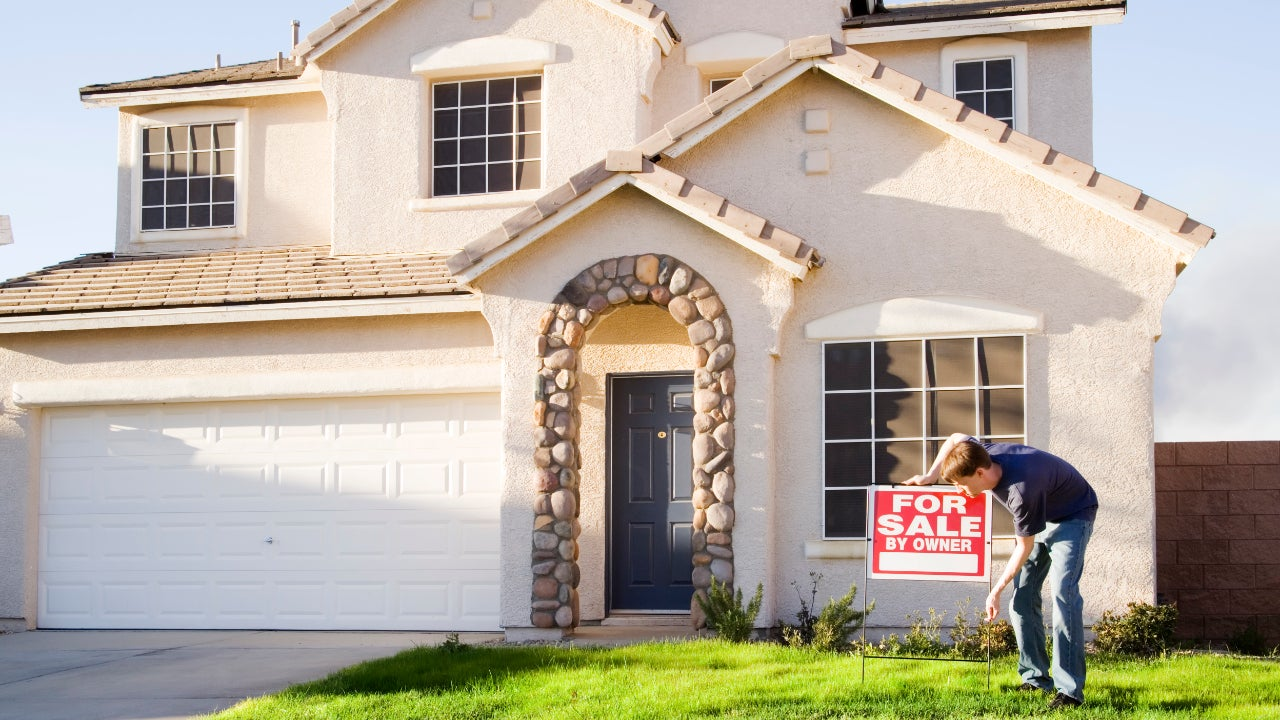 Home seller putting a for sale sign in yard