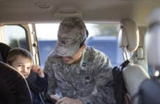 A female soldier in her battle dress uniform (BDU) buckles her son into his seat.