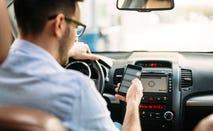 man using phone to check car insurance rates
