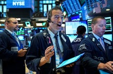 Traders on the floor of the New York Stock Exchange react to news