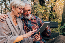 Senior couple looking at a tablet on a park bench