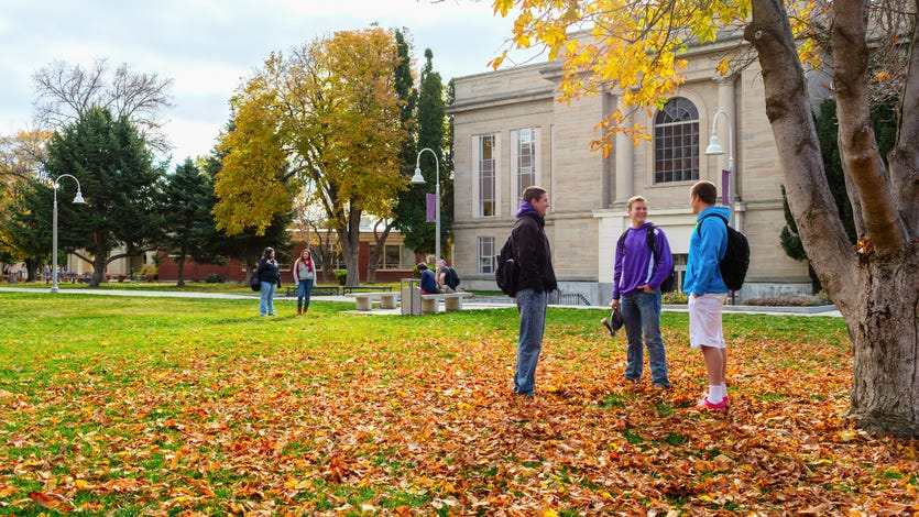 A photo of students talking on a college campus