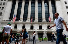 People pass the New York Stock Exchange