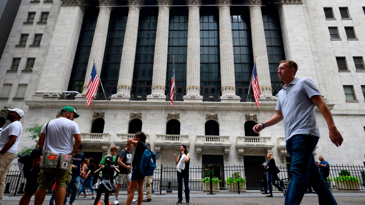 People pass the New York Stock Exchange