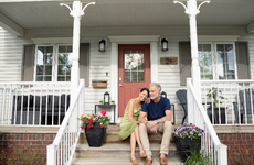 husband and wife sitting on the front steps of their house