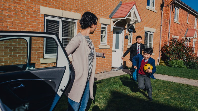 family leaving house and getting into car