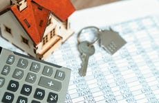 A calculator and house keys on top of financial records