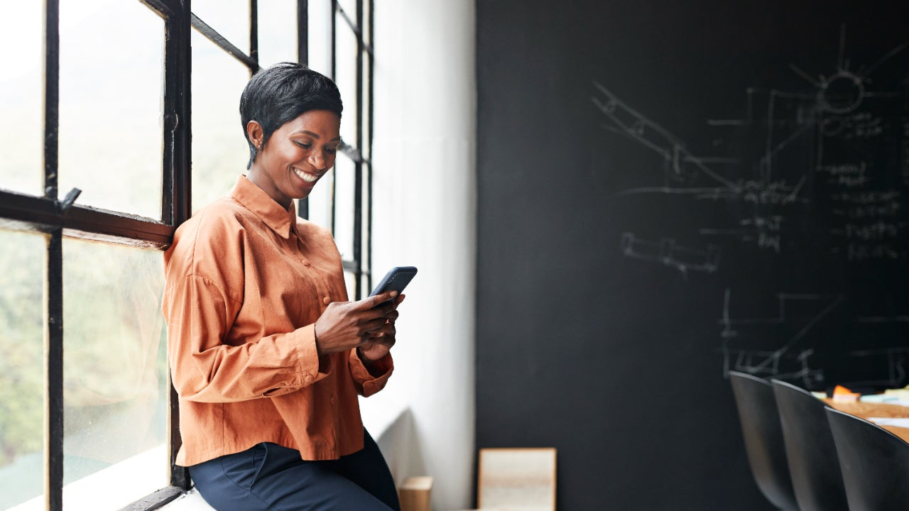 A woman holds a phone at an office