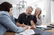 Financial advisor discussing paperwork with senior couple at dining table