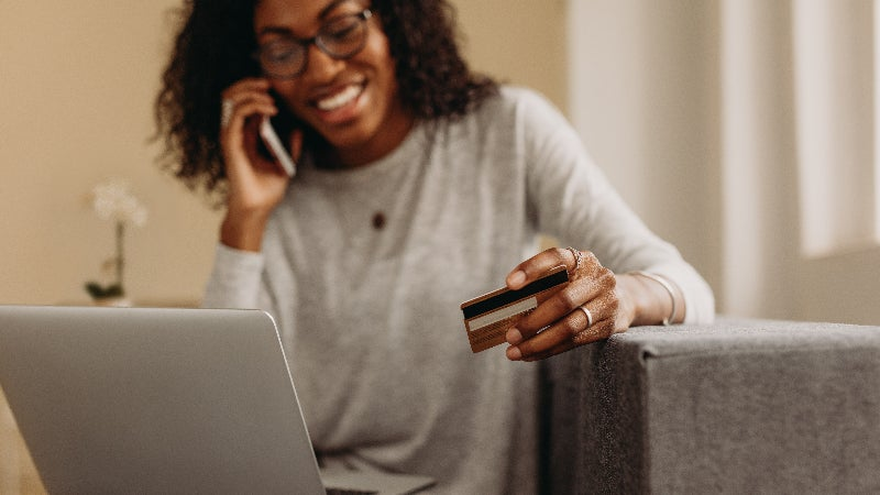 woman speaking on phone while holding credit card