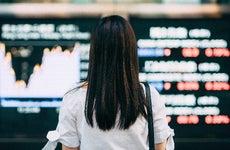 Woman looking at stock exchange market display screen