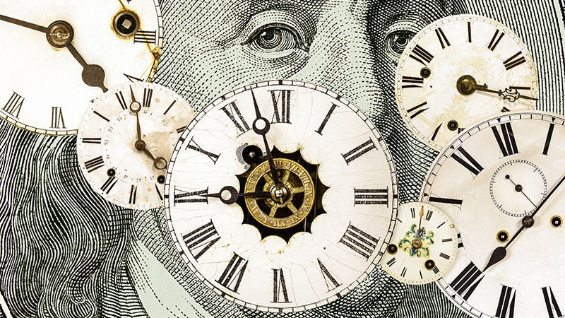 Clocks are displayed across an image of a dollar bill.