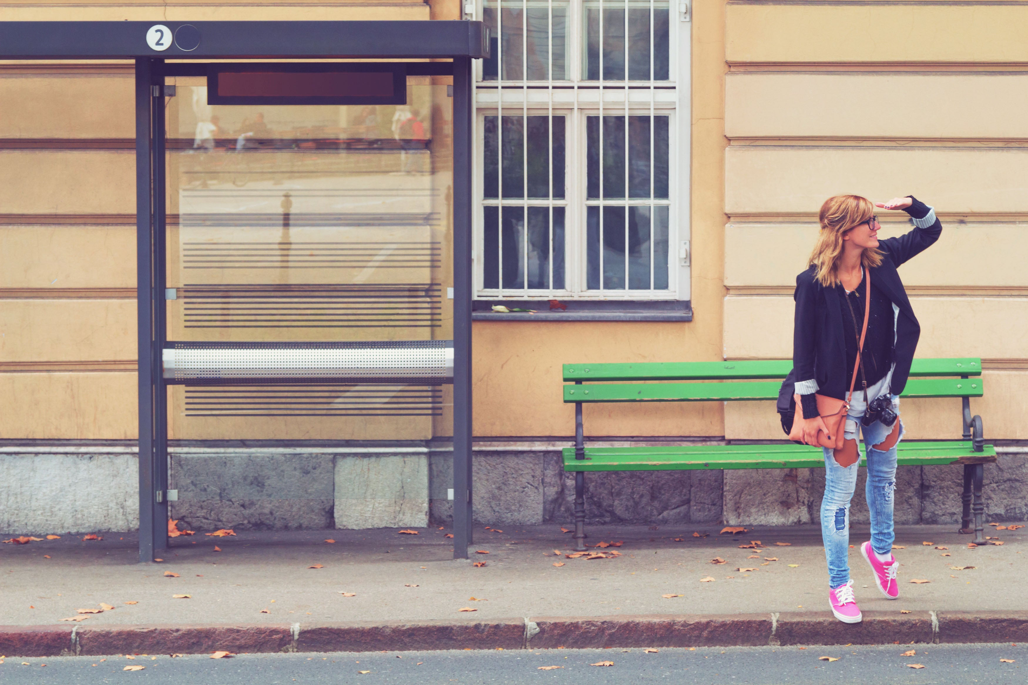 woman waiting at bus stop looking for bus