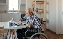 Disabled Senior Man in a Wheelchair Working From Home