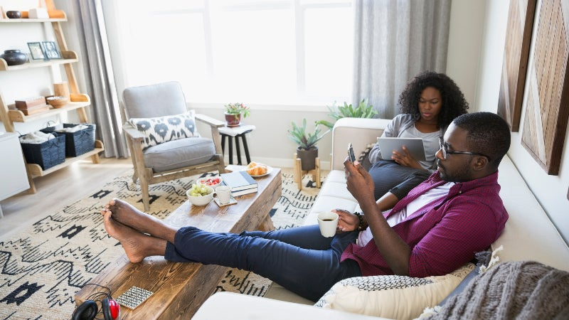 Couple drinking coffee using digital tablet and cell phone on living room sofa