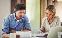 A man and a woman are sitting down at the kitchen table going over some financial forms.