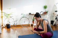 Young woman with smart phone on yoga mat in apartment