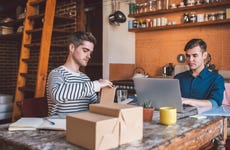 Young gay couple prepare packages for small business on kitchen table