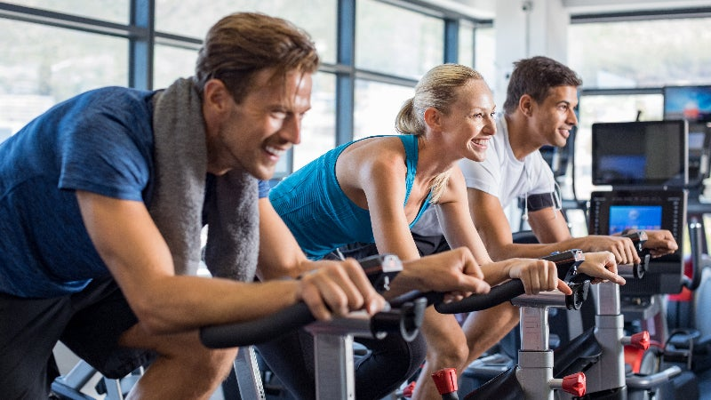 two men and a woman at the gym on stationary bikes