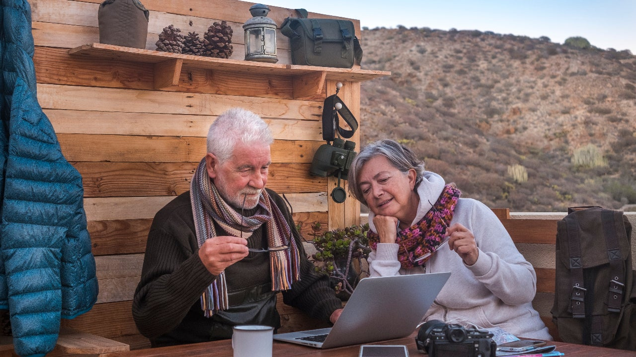 Two older adults research online.