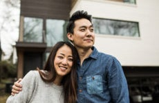 Portrait of young couple in front of home