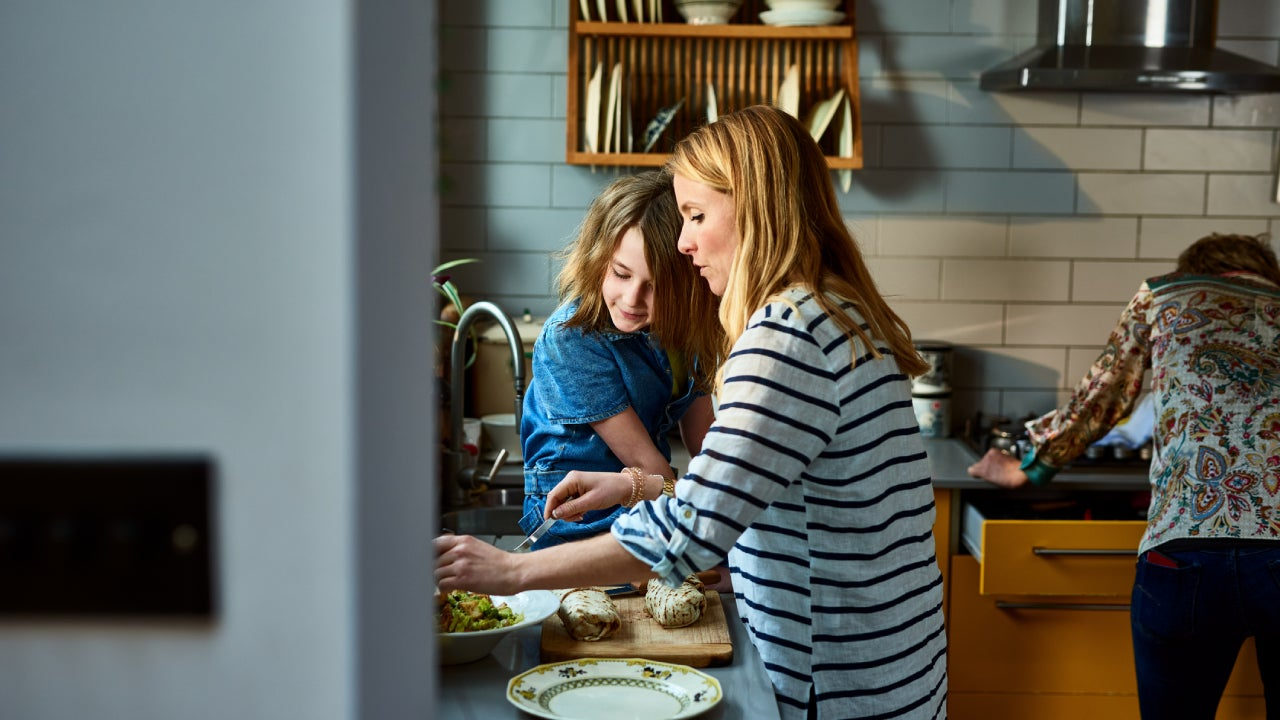 A mother and her daughter in the kitchen cooking up some food