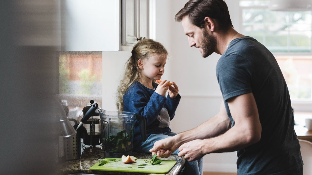 Side view of father cooking food while daughter having apple in kitchen
