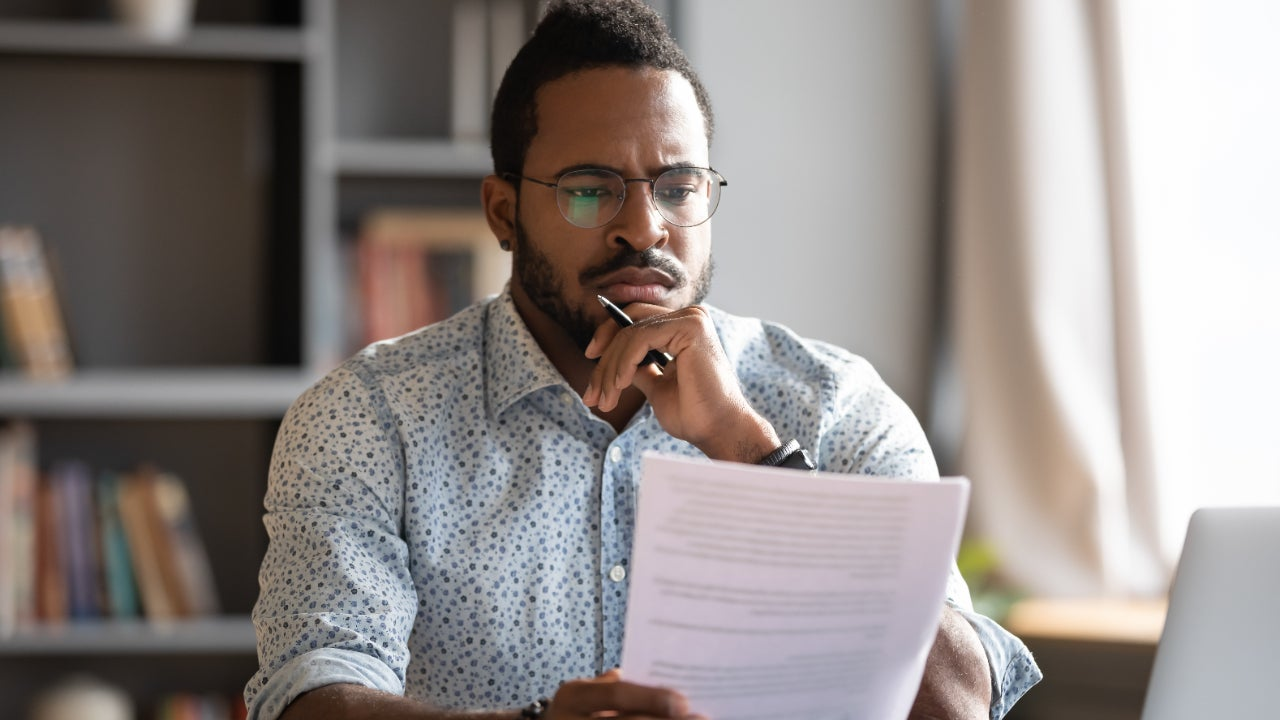 A confused man looks over paperwork.