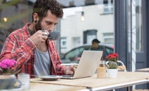 Male hipster working on laptop at cafe