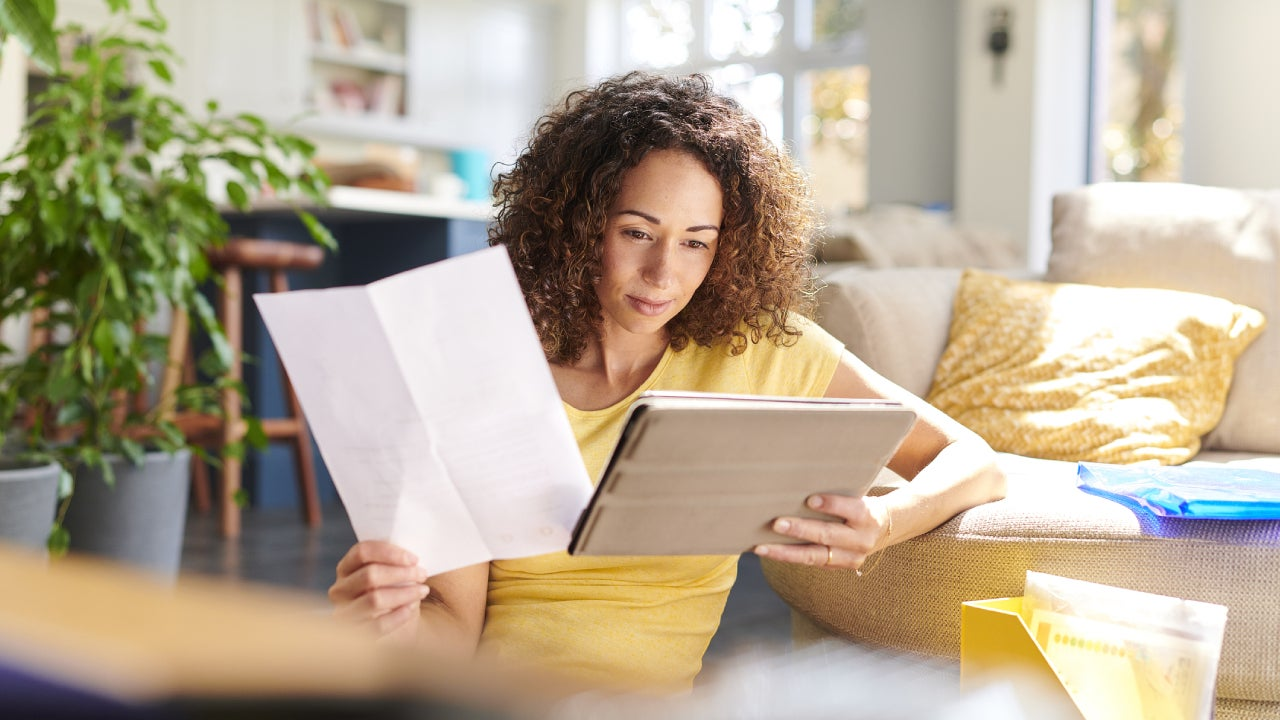 A woman in her living room holding a tablet in one hand and a piece of paper in the other. She is checking her home finances online.