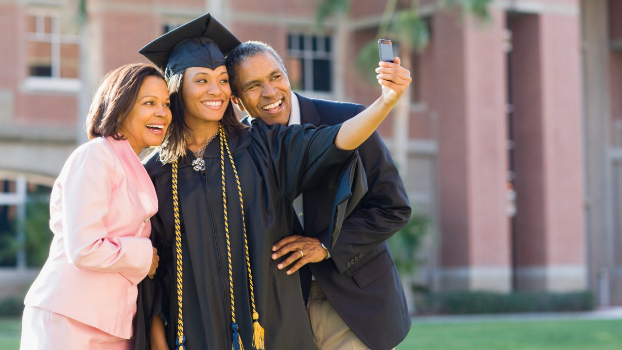 A young graduate woman takes a selfie with her parents