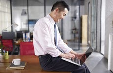 Businessman smiles while working on laptop.