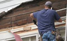 Man fixing home siding