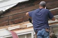 Man fixing home siding