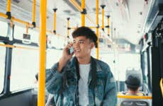 Man talking on phone while riding city bus