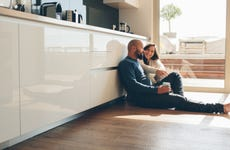 Couple sitting on floor of new home.