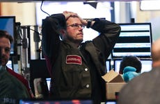 An exasperated stock trader holds his hands on his head