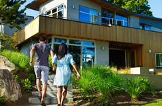 Man and woman running into modern house