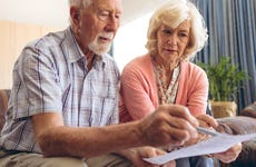 An older couple gestures to a financial contract