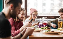 Group of young friends use smartphones to transfer funds for shared lunch